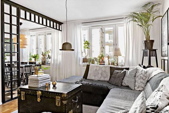старый сундук можно обшить кожей и поставить возле диванов