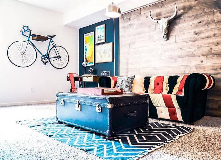 лофт в промышленном стиле с синим сундуком возле дивана