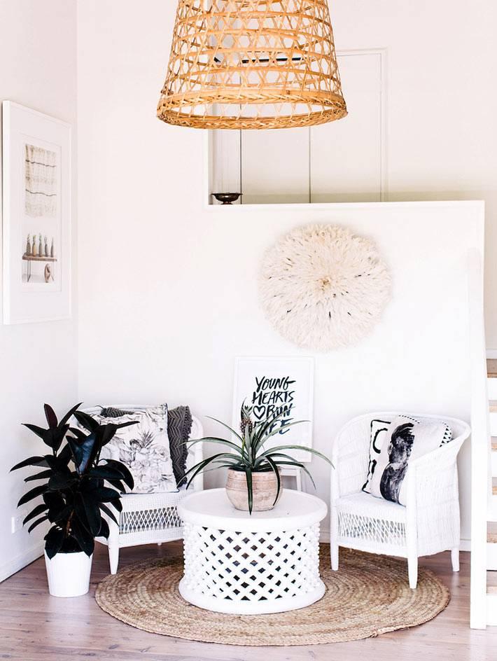 белый ажурный столик и пара плетеных кресел в доме