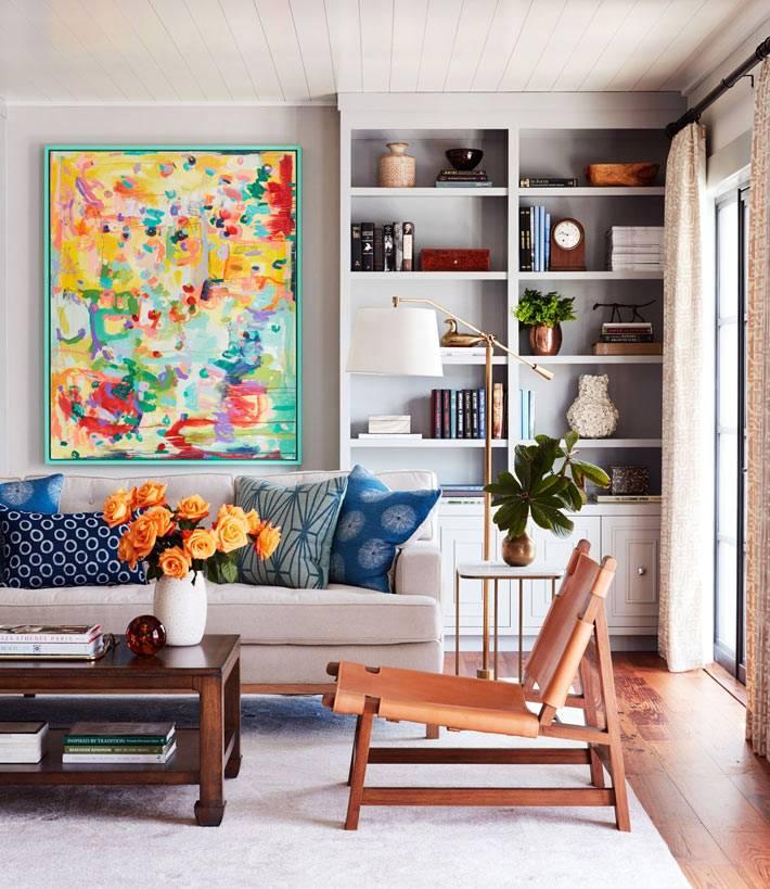 яркая картина и цветы украшают интерьер комнаты фото