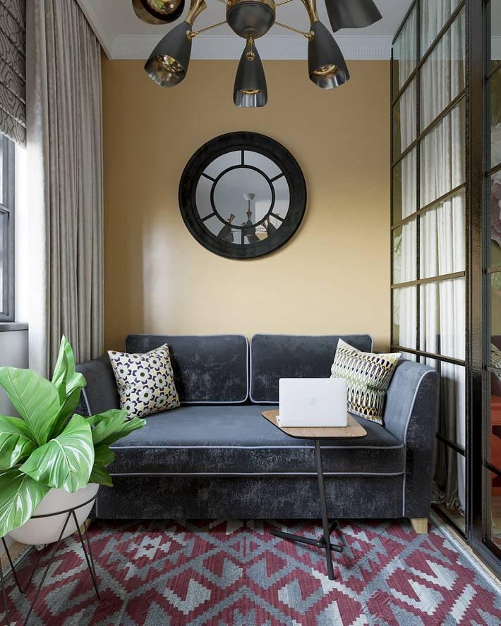 диван графитового цвета в зоне гостиной однокомнатной квартиры