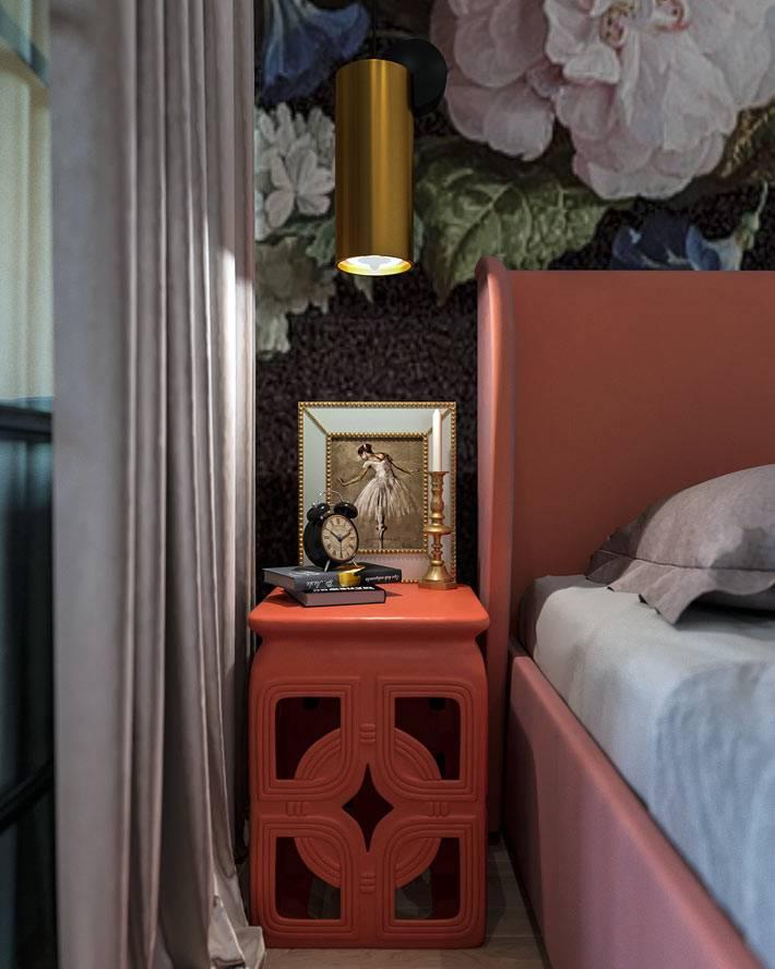 цветастые обои за розовым изголовьем кровати и оранжевая тумба