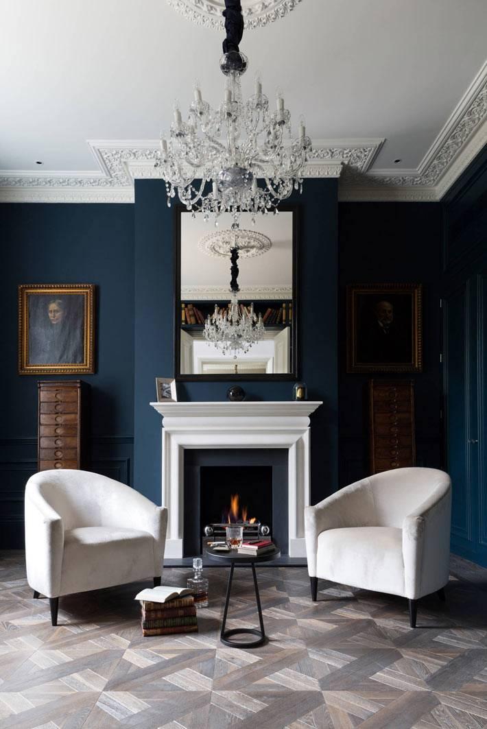 белые кресла и синие стены в комнате с лепниной на потолке