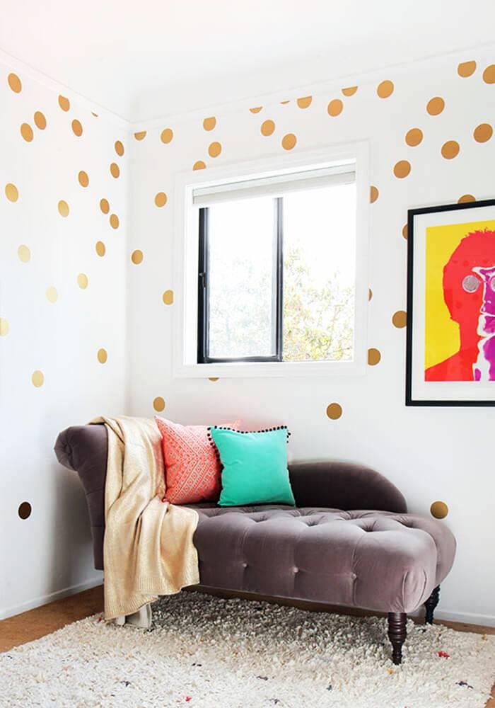 возле окна стоит красивая мягкая софа с яркими подушками