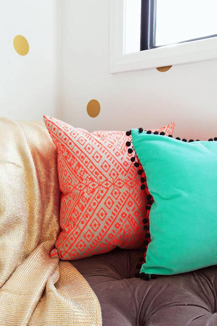 разноцветные декоративные подушки украшают нейтральный интерьер комнаты