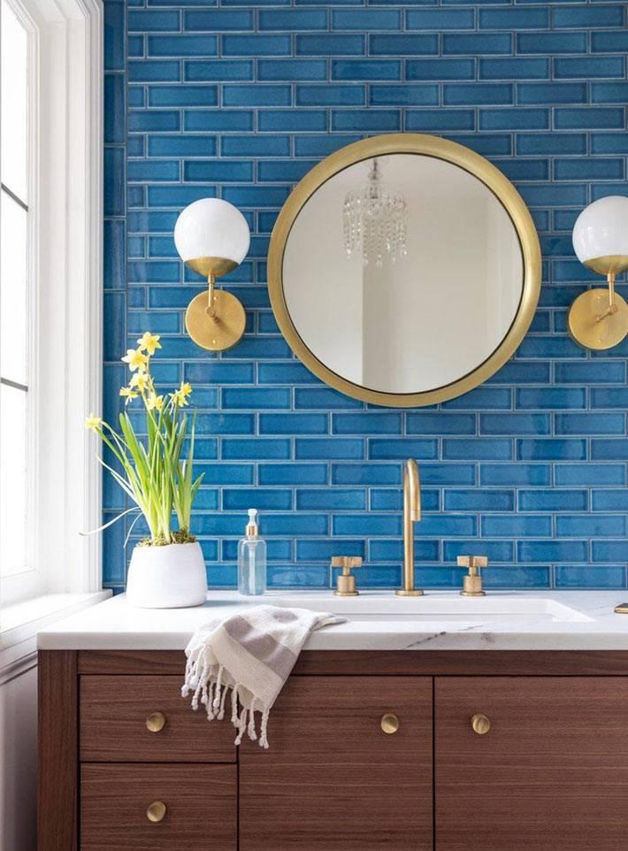 синяя кирпичная стена и латунные аксессуары в ванной