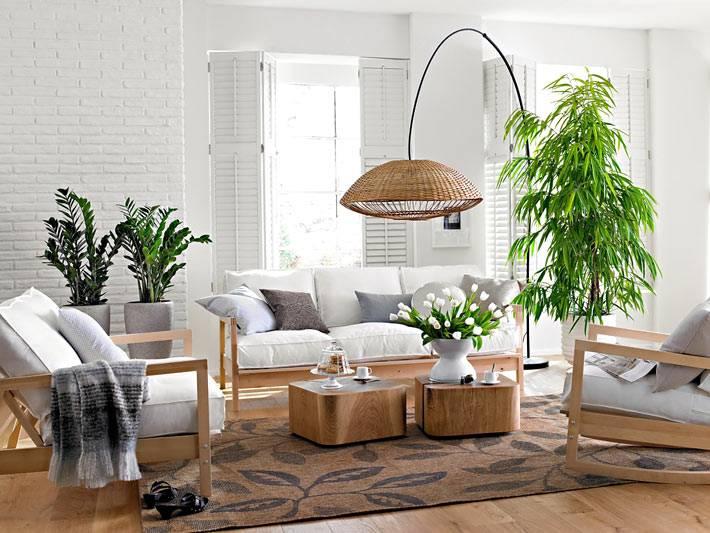 современная гостиная с белыми кирпичными стенами и зелеными растениями