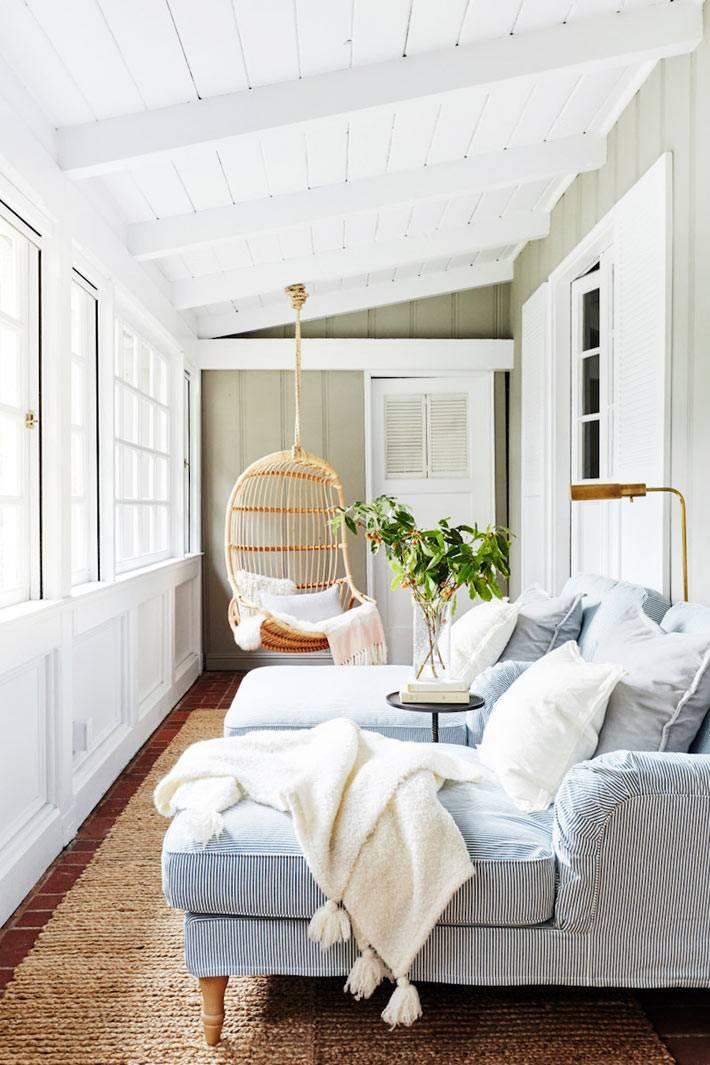 закрытая тдеревянная терраса с плетеным подвесным креслом