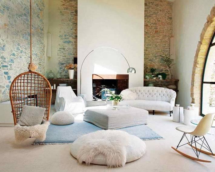 гостиная с белой мебелью, кирпичными стенами и висячим креслом-качелью