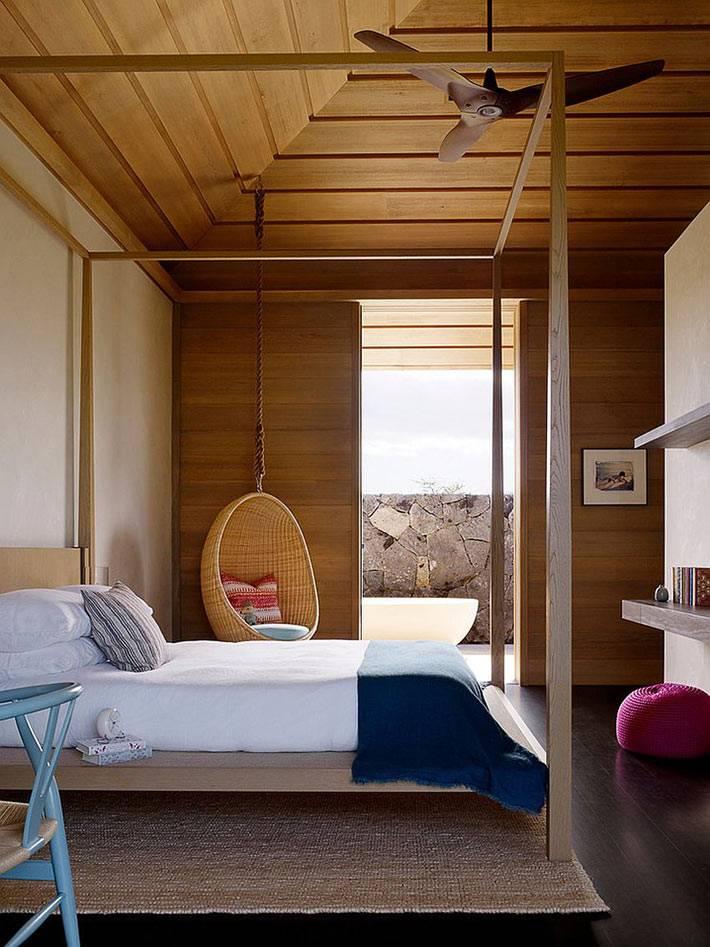 спальня с деревянными стенами и потолком, кресло-кокон возле кровати