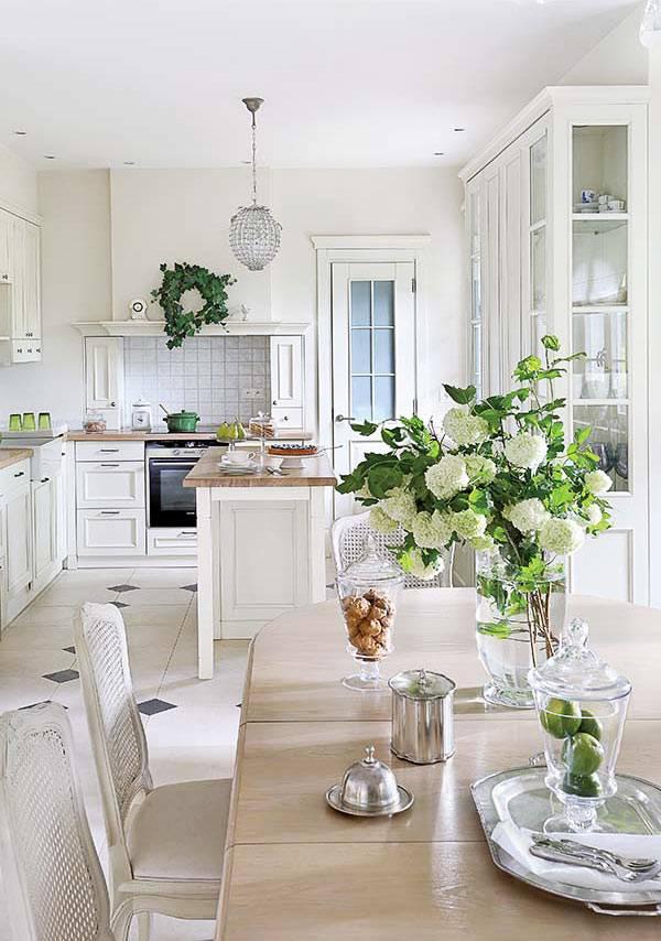 белый интерьер кухни украшен живыми цветами в вазах и на стенах