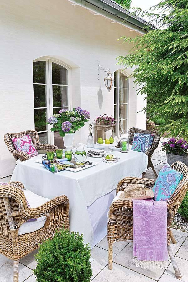плетёные кресла и обеденный стол во дворе дома