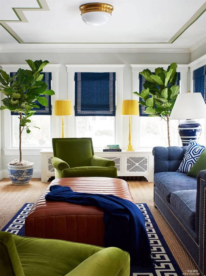 солнечная гостиная комната с синим диваном и зелеными креслами