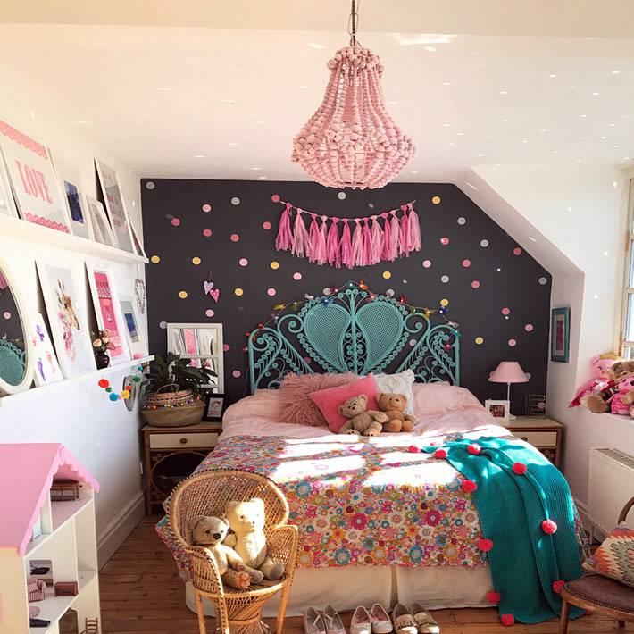 черная акцентная стена с яркими конфетти и розовая люстра в детской