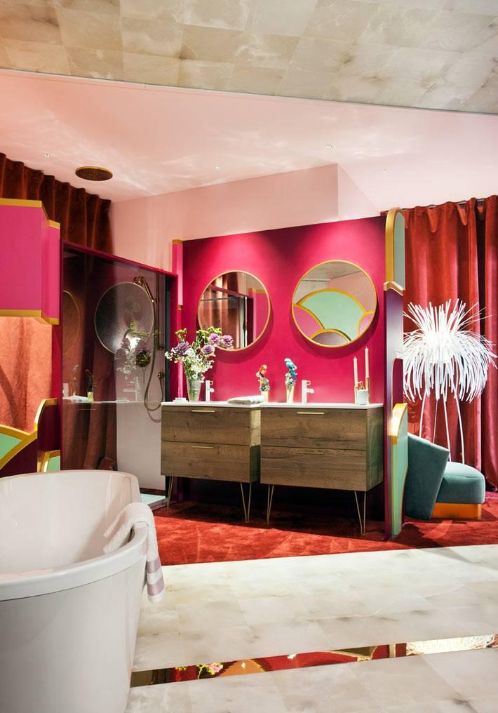 круглые зеркала на розовой стене над раковиной в ванной
