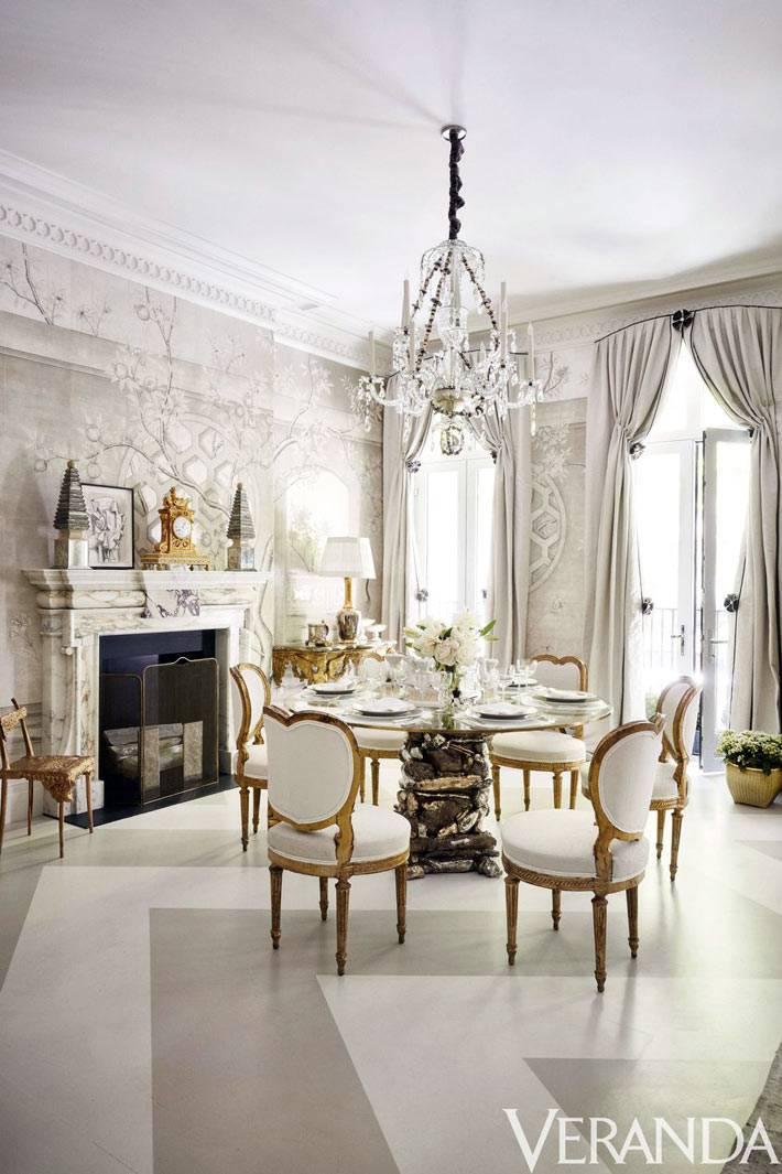 роскошная столовая комната с камином и хрустальной люстрой
