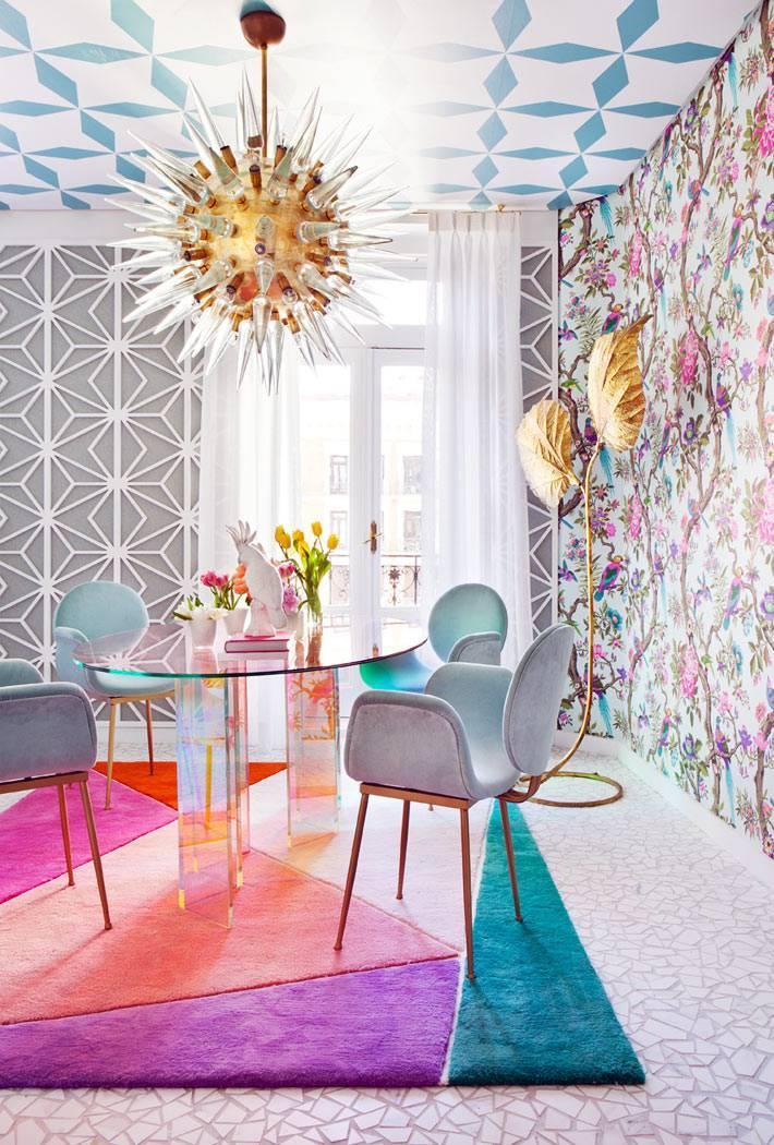 стеклянный стол и мягкие кресла на ярком ковре в обеденной зоне