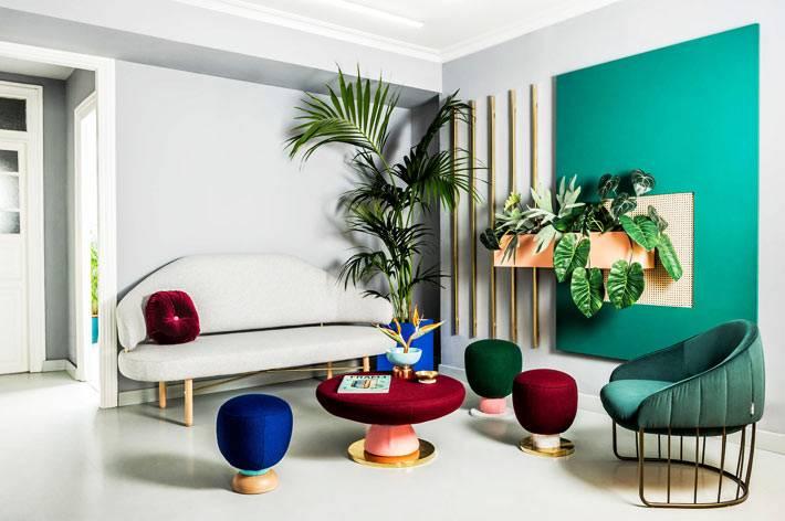 белый диван на ножках и зеленое кресло на фоне зеленой стены с растениями