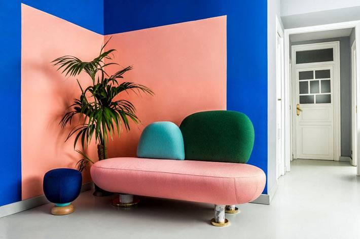 креативный разноцветный диван и синий пуфик в углу комнаты