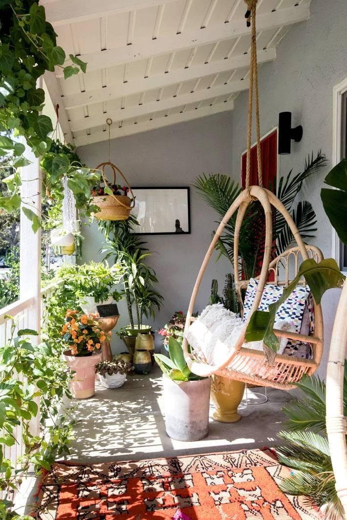подвесное ротанговое кресло и зеленые растения на террасе