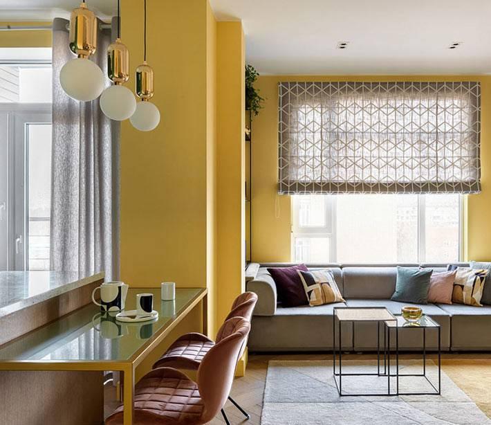 удобный диван под окном с римскими шторами