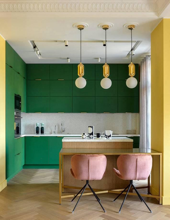 кухонный гарнитур насыщенного зелёного цвета и розовые стулья