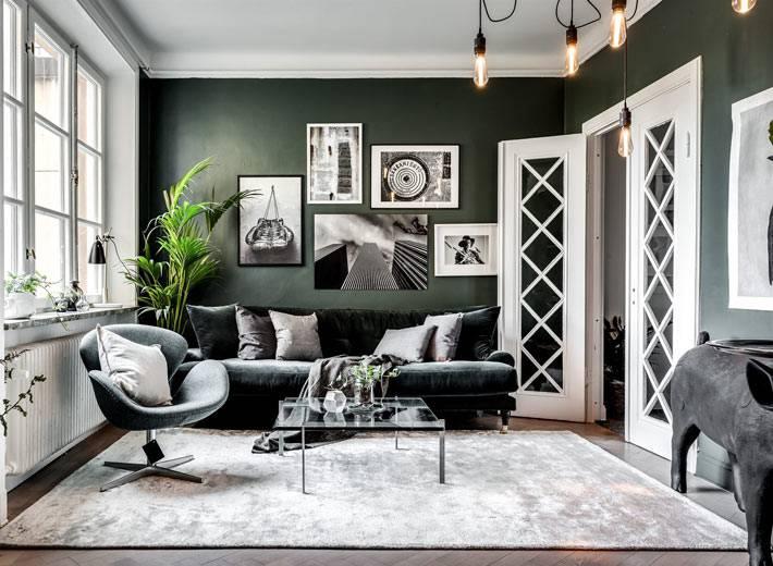комната с темно-зелеными стенами и черной мягкой мебелью