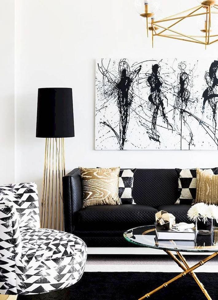 черный диван и золотистая фурнитура на люстре, торшере и столике