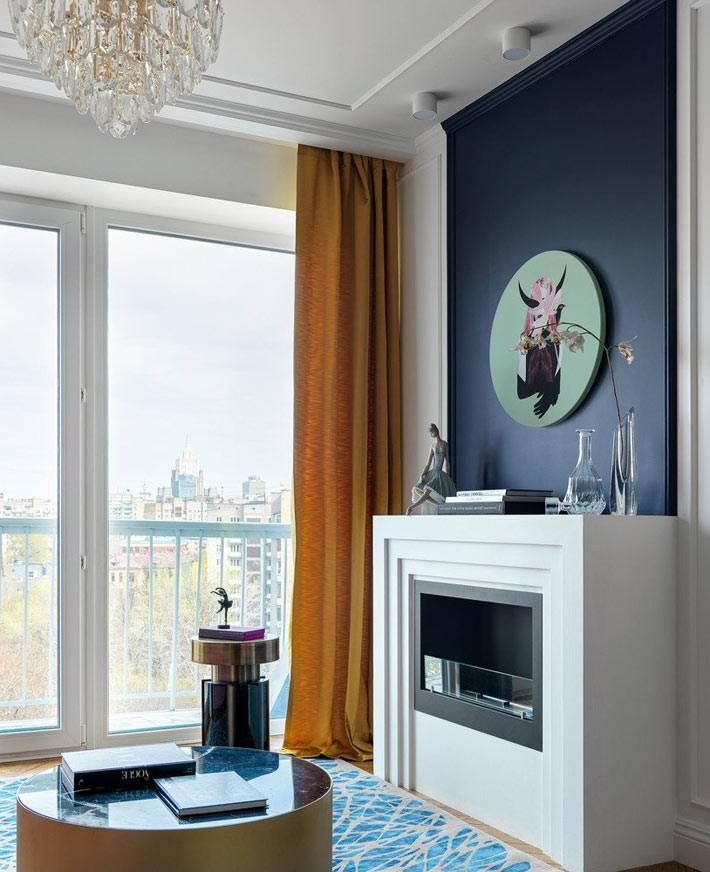 белый фальш-камин, синий портал над камином в комнате