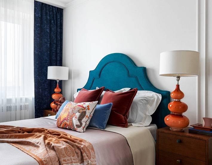 мягкое синее изголовье кровати, оранжевые настольные лампы