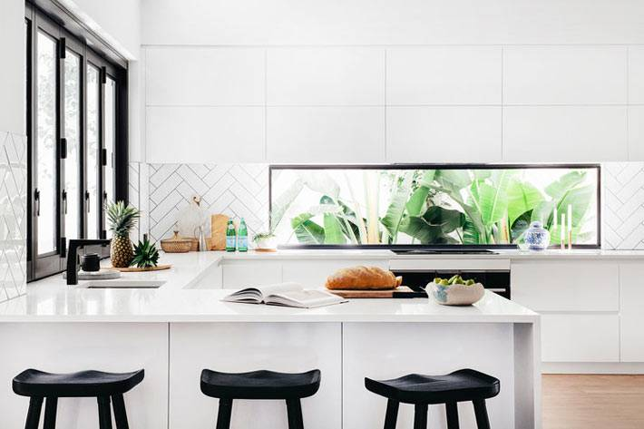 минимум мебели на белой кухне с черными стульями