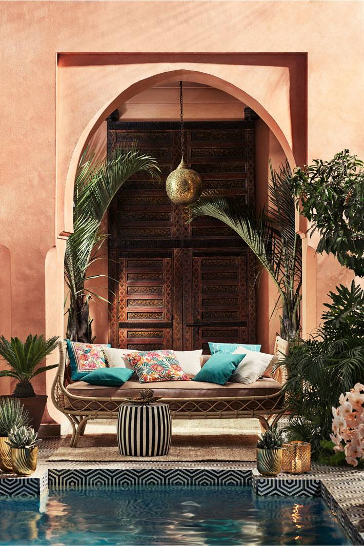 плетеный диванчик из ротанга с цветными подушками возле бассейна