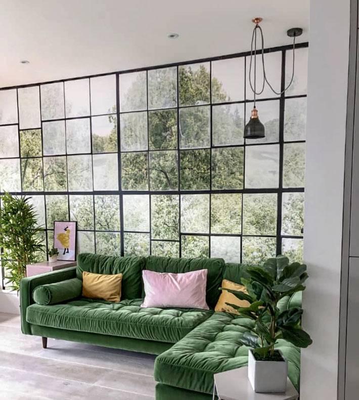 зелёный мягкий угловой диван, стеклянная стена в комнате