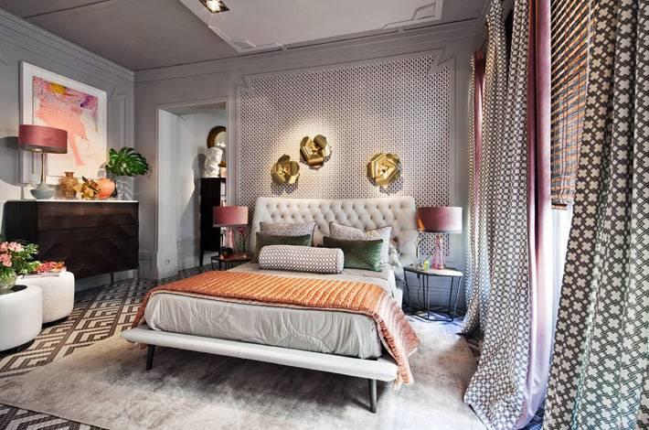 уютная спальня с большой кроватью с высоким мягким изголовьем