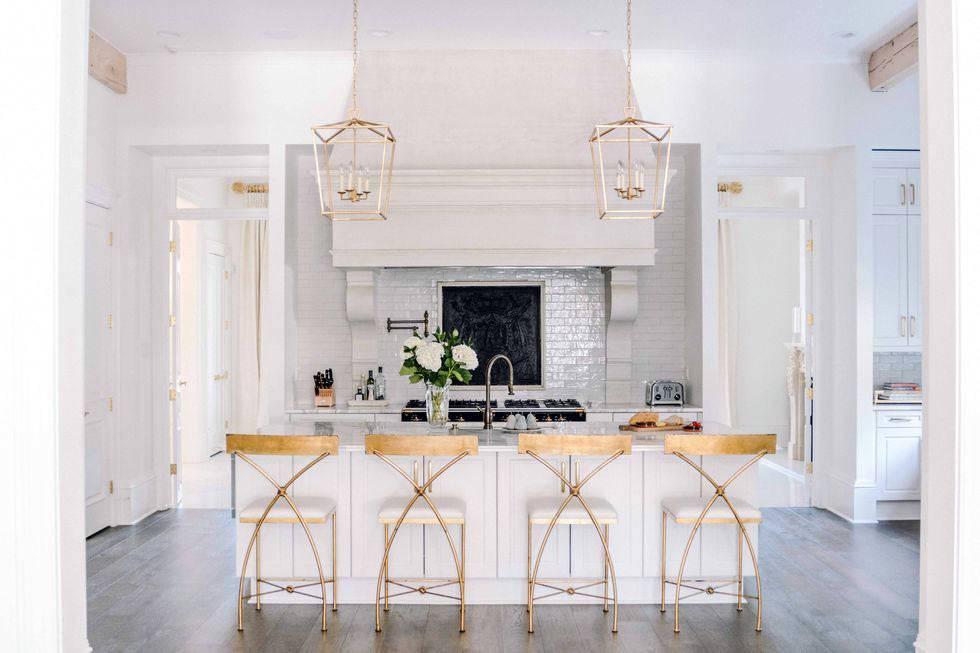 белый цвет и золото в оформлении большой кухни в загородном доме
