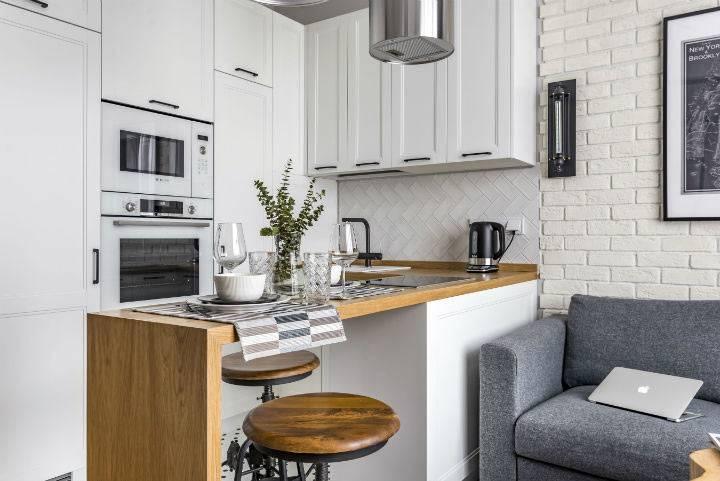 деревянная барная стойка и стулья в конрасте с белым кухонным гарнитуром