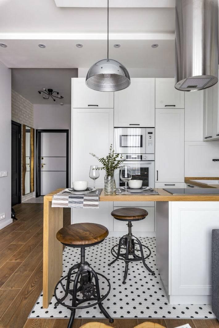 пол на кухне выложен белой и черной мозаичной плиткой