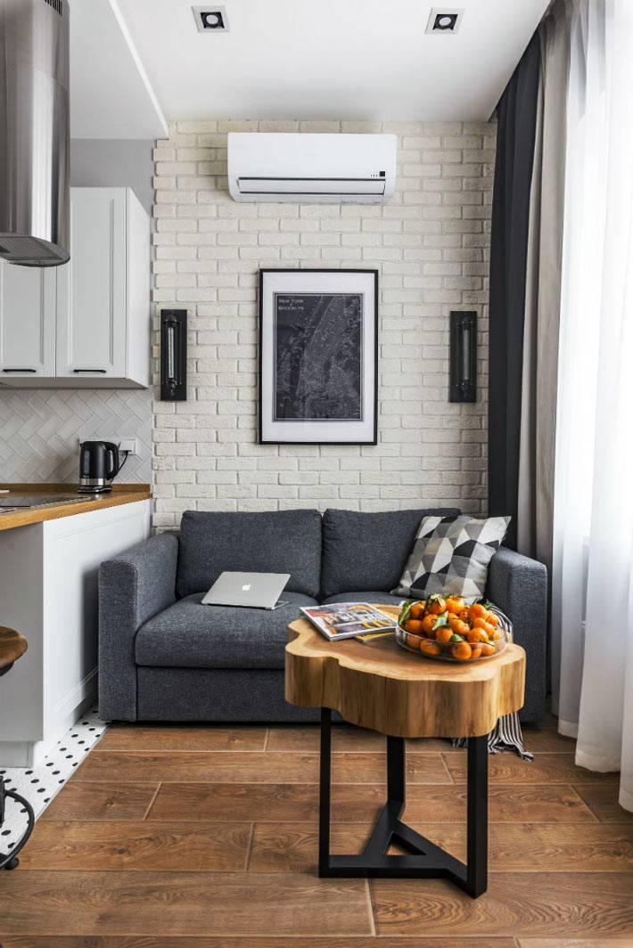 самодельный кофейный столик из сруба дерева возле серого дивана