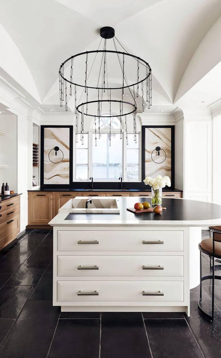белый полукруглый остров на кухне с черным полом