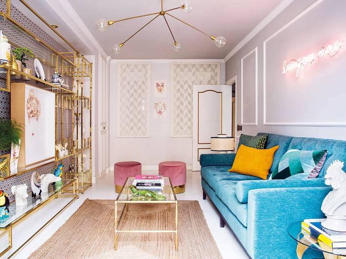 синий диван и розовые пуфы в эеклектичной гостиной