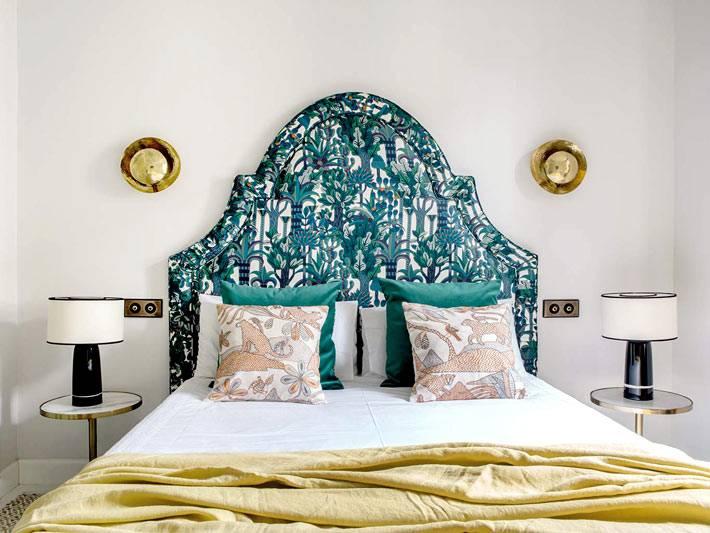 кровать в спальне с высоким зелёным изголовьем