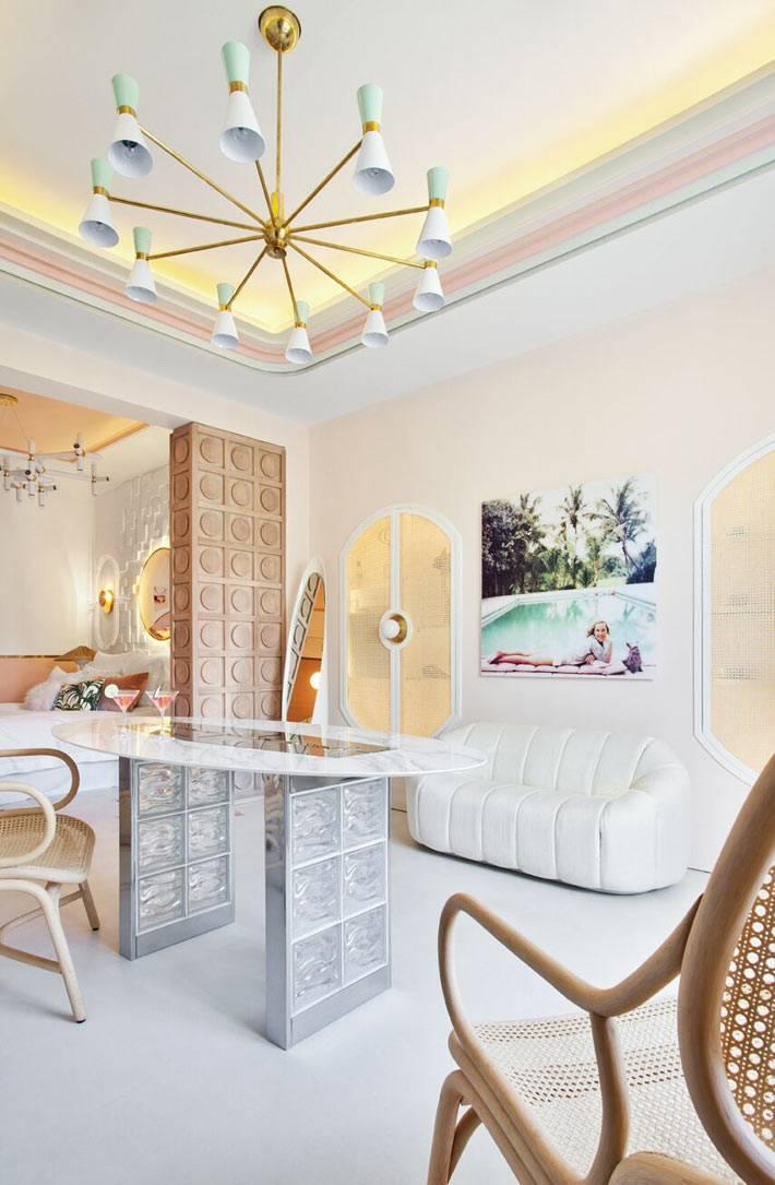 белый кожаный диван, овальный стол из стеклоблоков, деревянные стулья