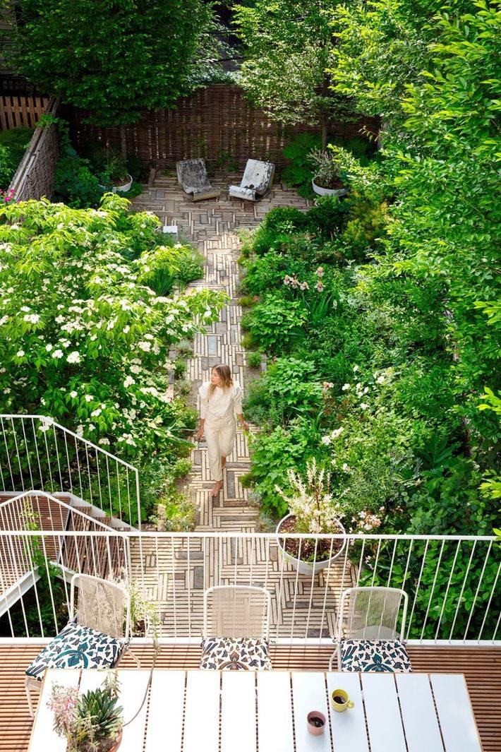 маленький уютный двор с зелёными деревьями и деревянным настилом