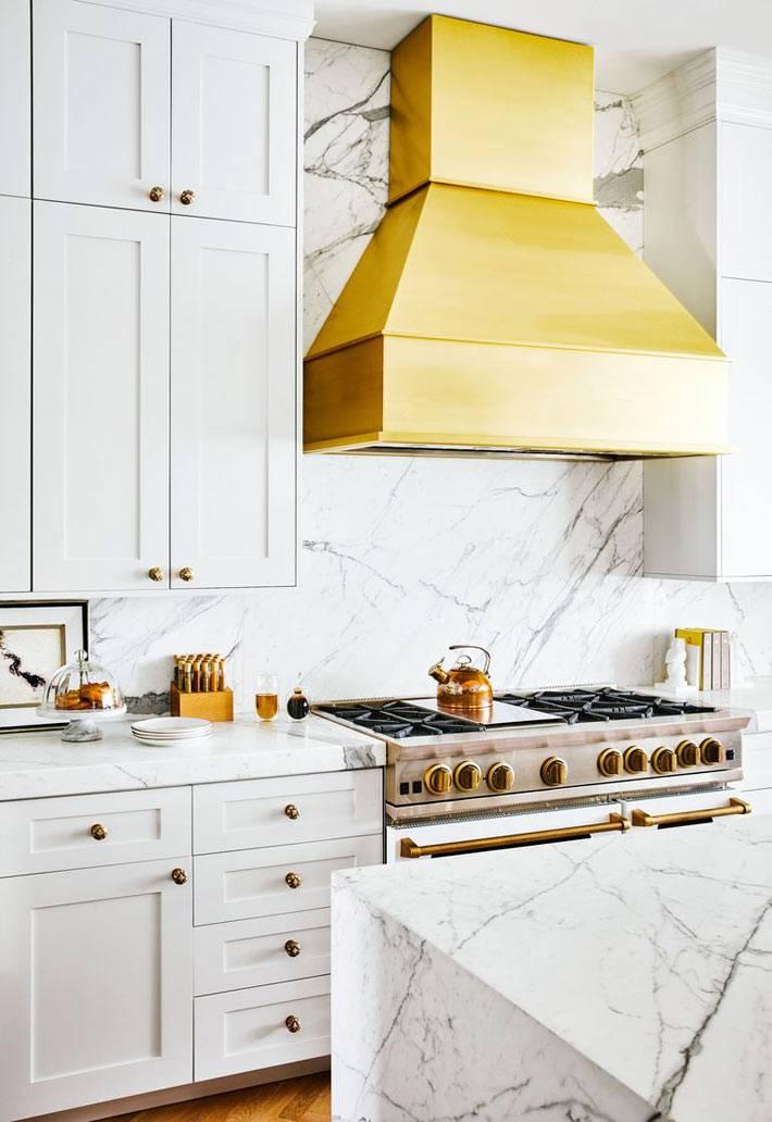 белые кухонные шкафчики, мраморная столешница, золотистая вытяжка