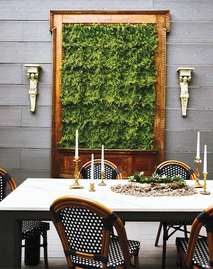 терраса с большим столом и вертикальным озеленением стены дома