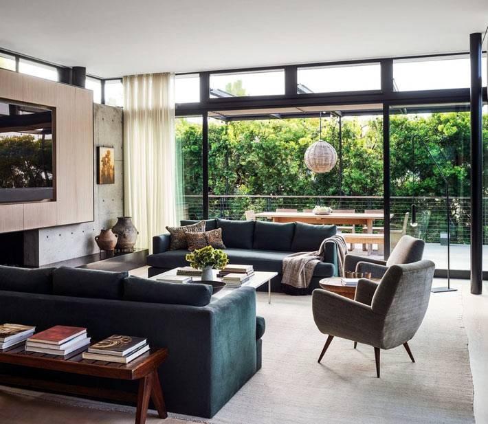 Возле большого экрана в гостиной расположены массивные диваны и кресла