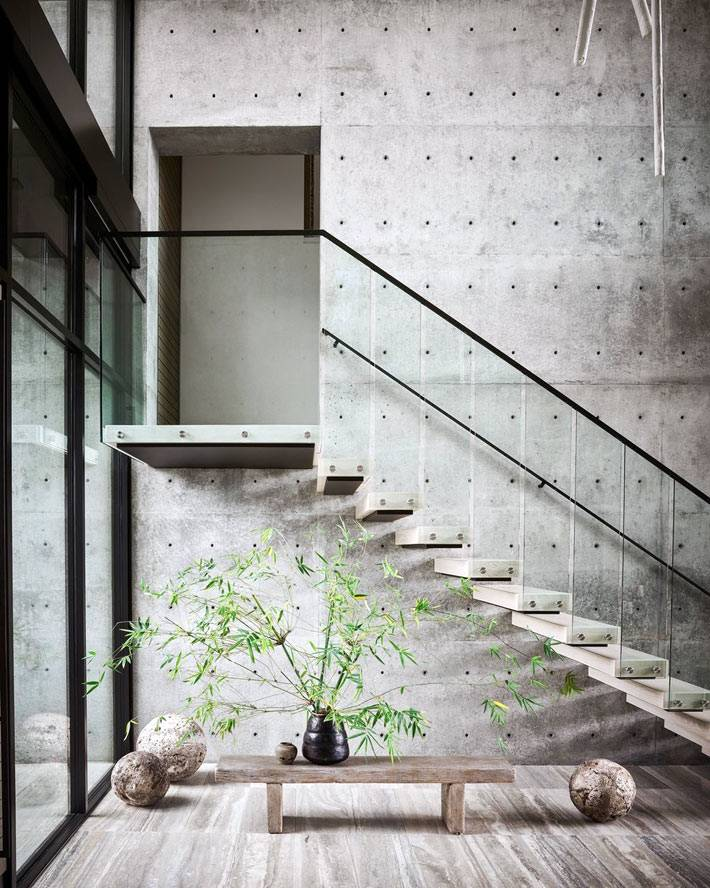 Деревяные ступеньки как бы сливаются с фактурой бетонных стен