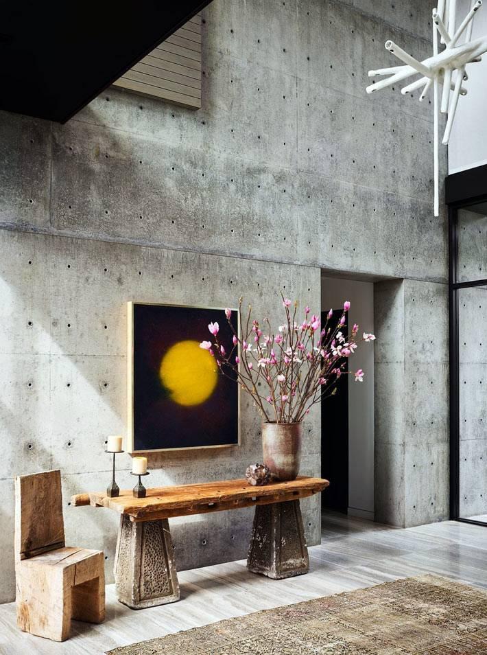 Прихожая с бетонныи стенами, масивный деревянный стол.