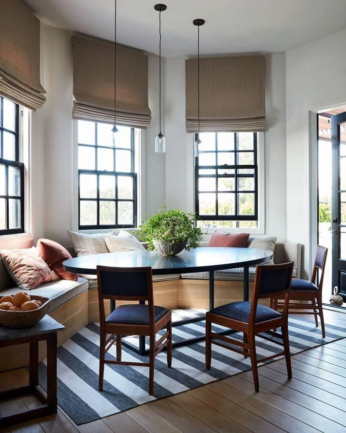 обеденный стол в зоне эркера, окна с чёрными рамами фото