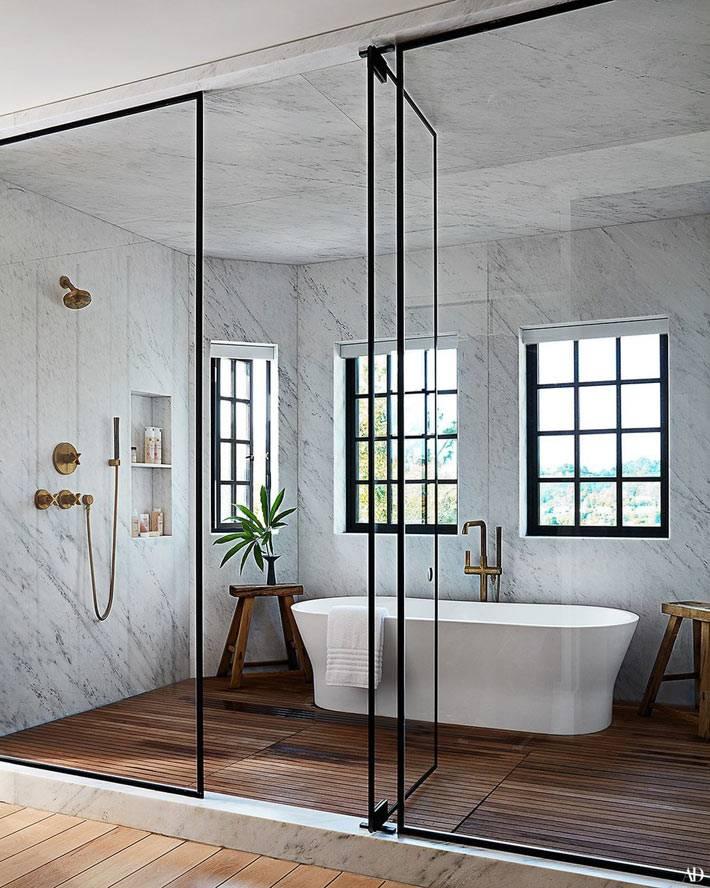 зона ванной с мраморными стенами за стеклянной перегородкой